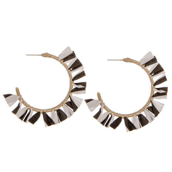 "Large hoop earrings featuring black and white tassel accents. Approximately 2"" in diameter."