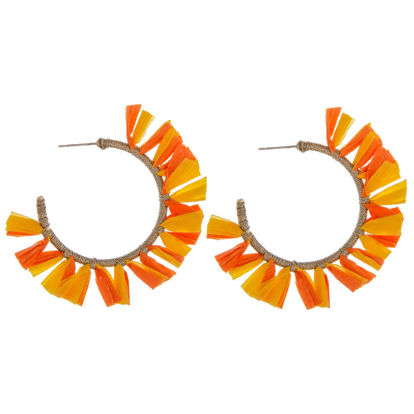 "Large hoop earrings featuring orange and yellow tassel accents. Approximately 2"" in diameter."