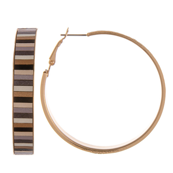 "Large gold metal hoop earrings featuring resin details. Approximately 2"" in diameter."