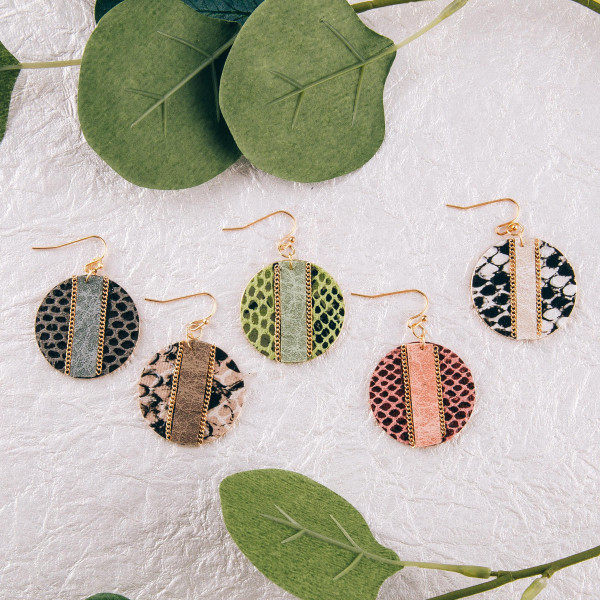 """Metal plated disc earrings featuring faux leather snakeskin with a raised faux leather center detail and gold chain inspired accents. Approximately 1.5"""" in diameter."""