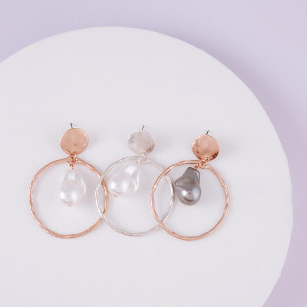 """Metal circular earrings featuring a drop pearl accent with a stud post. Approximately 2"""" in length."""