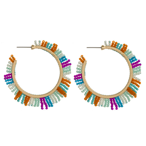 "Large open hoop earrings featuring seed beaded tassel details. Approximately 2"" in diameter."