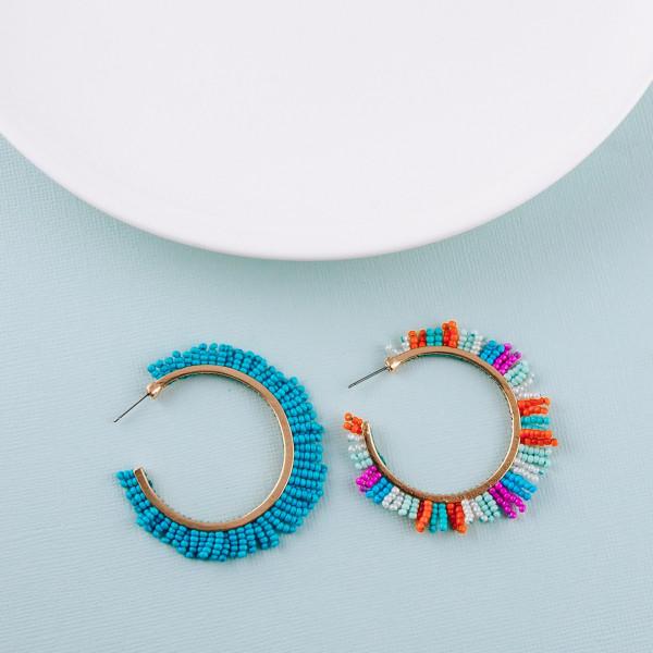 "Large open hoop earrings featuring seed beaded tassel details. Approximately 2"" in diameter."