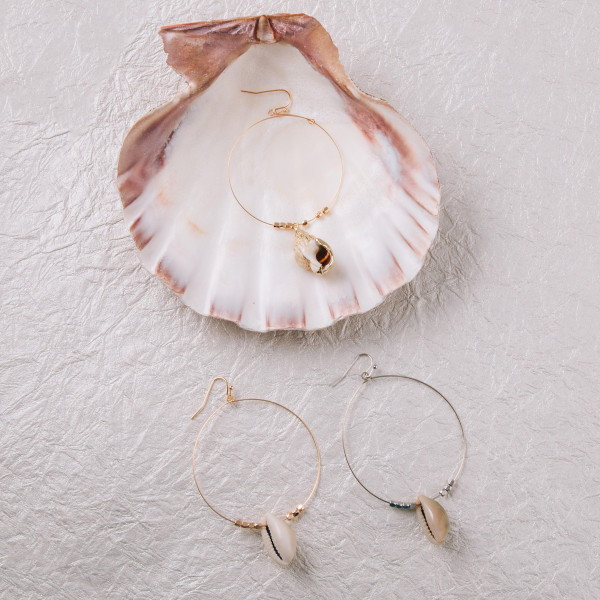 "Large circular earrings featuring a puka shell detail with beaded accents. Approximately 2"" in diameter."