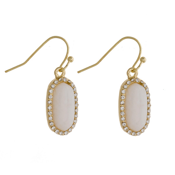 "Dainty metal drop earrings featuring a natural stone accent and cubic zirconia details. Approximately .75"" in length."