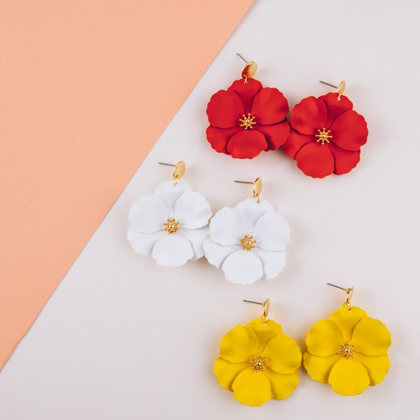 "Metal flower earrings featuring a gold center accent. Measures approximately 1.5"" in diameter."
