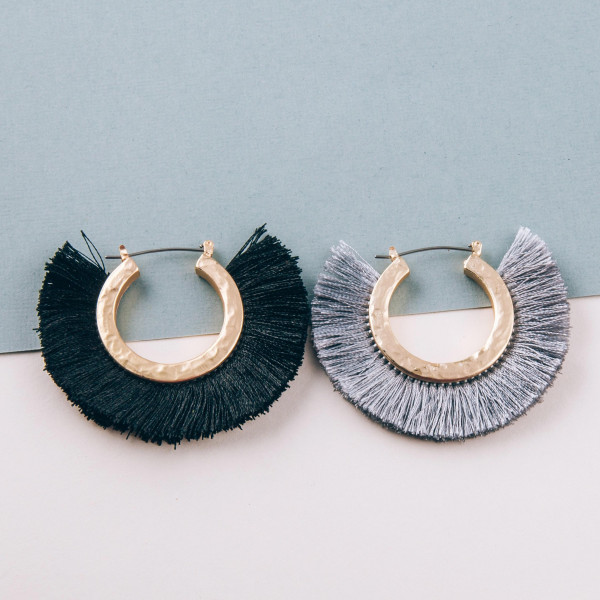 "Gold metal hoop earrings featuring black tassel detailing. Approximately 2"" in diameter."