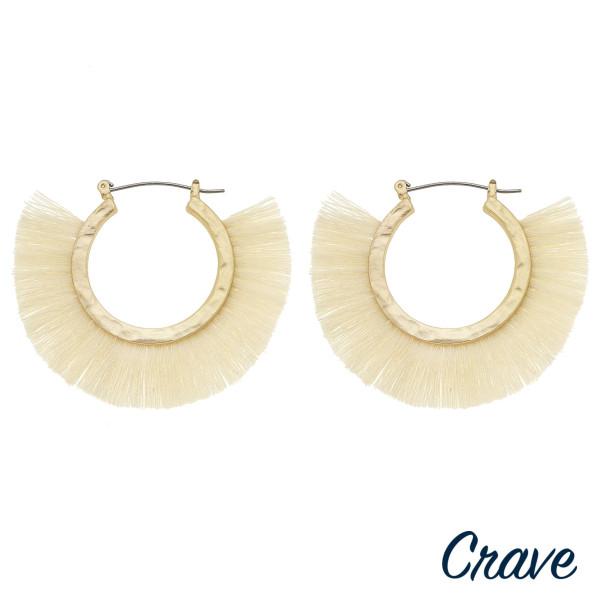 """Gold metal hoop earrings featuring ivory tassel detailing. Approximately 2"""" in diameter."""