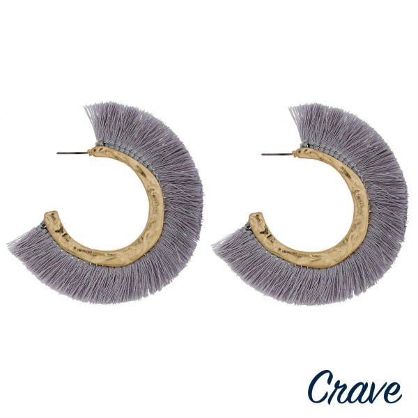 "Large hoop earrings featuring grey fabric tassel details with gold metal accents. Approximately 2.5"" in diameter."
