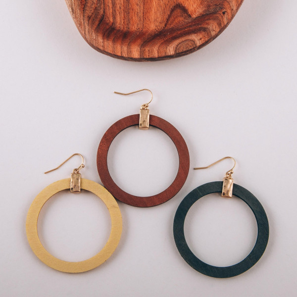"""Large wood circular drop earrings featuring a gold metal accent. Approximately 2"""" in diameter."""