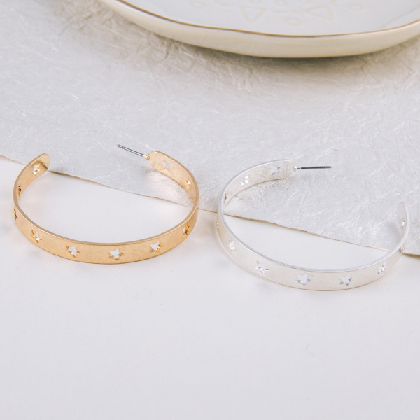 """Large metal hoop earrings featuring cut out star details. Approximately 2"""" in diameter."""