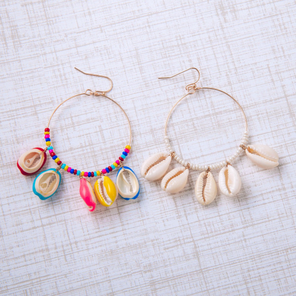"Gold circular earrings featuring puka shell accents and bead details. Approximately 1.5"" in diameter."