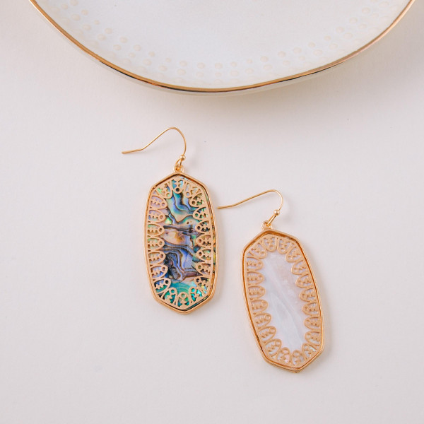 "Long metal earrings featuring mother of pearl inspired details and gold accents. Approximately 1.5"" in length."