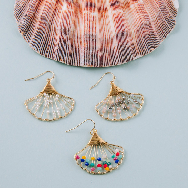 "Gold wire wrapped seashell earrings with natural beaded accents. Approximately 1"" in length."