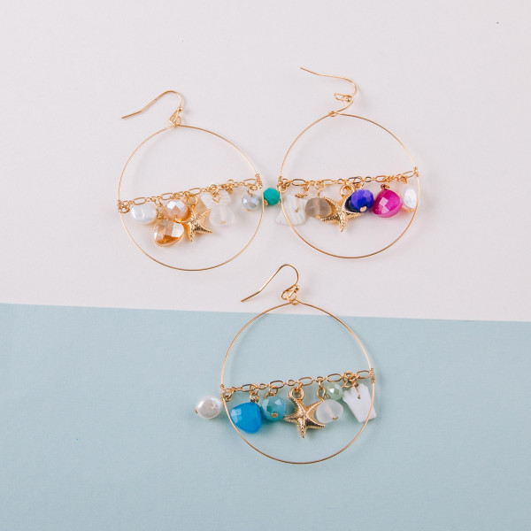 "Circular metal earrings featuring a center chain detail with pearl, bead and starfish accents. Approximately 2"" in length."
