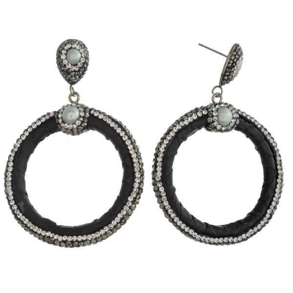 """Circular faux leather earrings featuring rhinestone details and pearl accents with a stud post. Approximately 2.5"""" in length."""