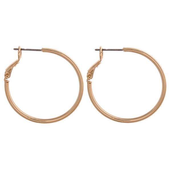 """Small gold metal hoop earrings. Approximately 1"""" in diameter."""