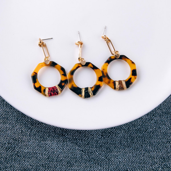 "Resin drop earrings featuring a snakeskin accent with wire wrapped details and a stud post. Approximately 2"" in length."