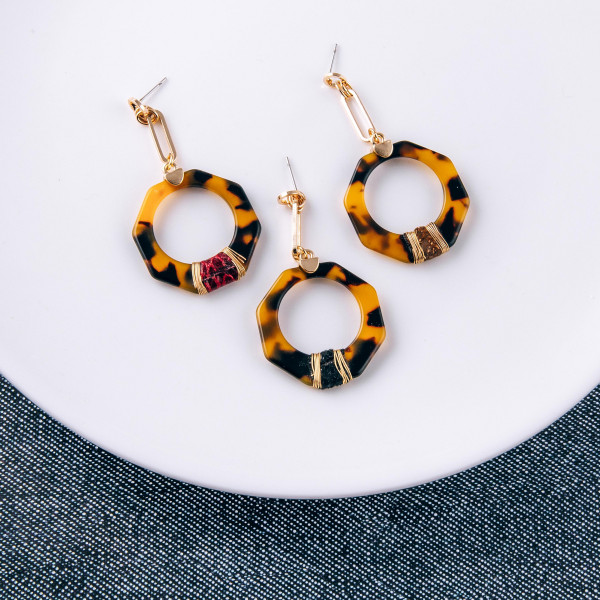 """Resin drop earrings featuring a snakeskin accent with wire wrapped details and a stud post. Approximately 2"""" in length."""