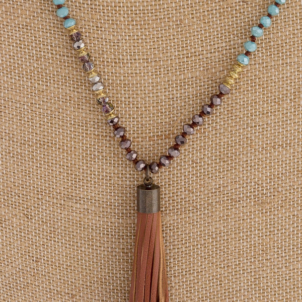 "Long iridescent beaded necklace featuring a tassel pendant. Pendant approximately 4"". Approximately 38"" in length overall."