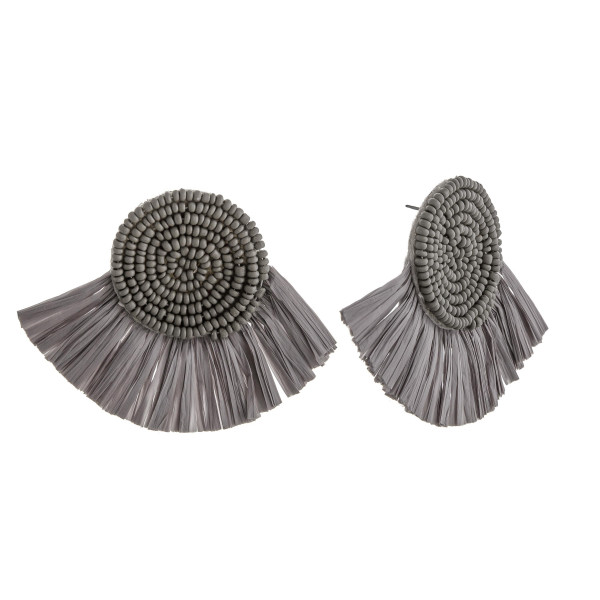 "Seed beaded felt disc earrings featuring raffia tassel details. Approximately 2"" in length."