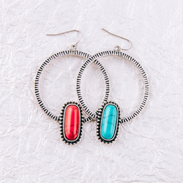 """Metal circular earrings featuring a natural stone oblong accent. Approximately 3"""" in length."""