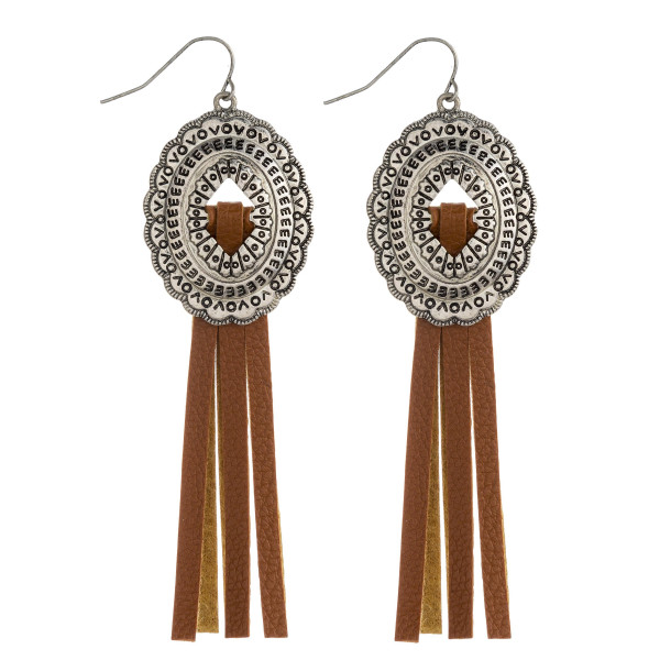 "Faux leather tassel earrings featuring a metal oval inspired detail. Approximately 3.5"" in length."