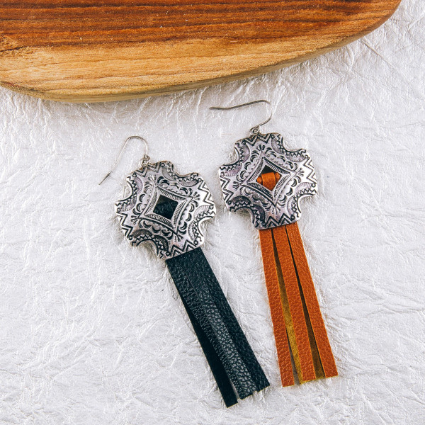 "Faux leather tassel earrings featuring a metal cross inspired detail. Approximately 3.5"" in length."