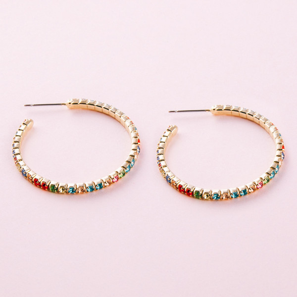 "Gold hoop earrings featuring multicolor cubic zirconia details. Approximately 1"" in diameter."