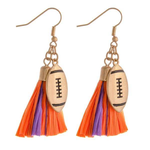 "Raffia tassel drop earrings featuring a gold metal football accent. Approximately 2"" in length"