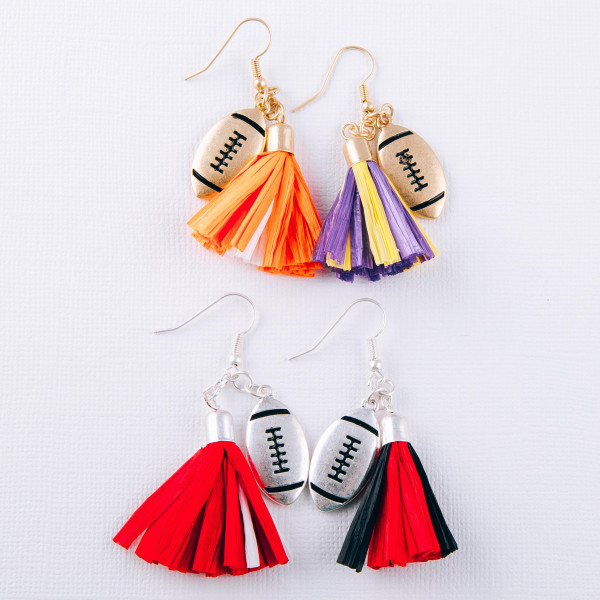 "Raffia tassel drop earrings featuring a silver metal football accent. Approximately 2"" in length"