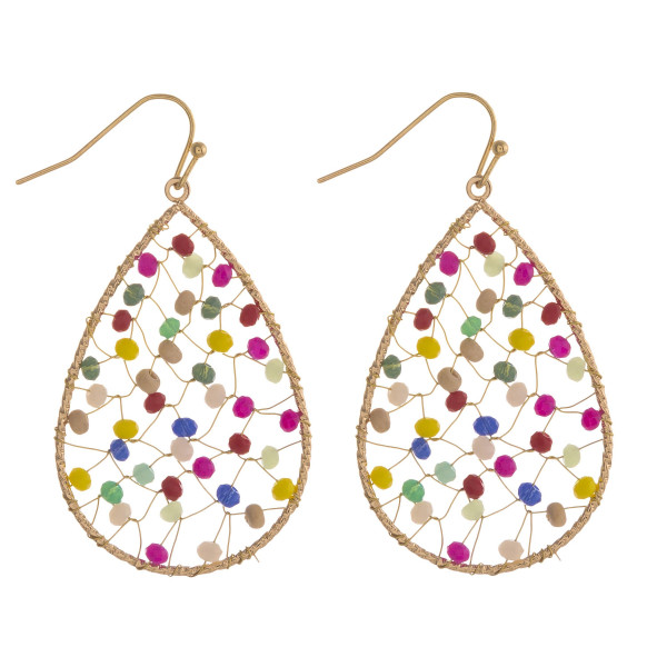 "Metal teardrop earrings featuring iridescent beaded center details. Approximately 2"" in length."