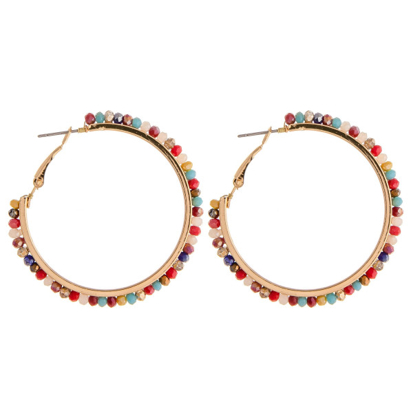 "Metal hoop earrings featuring faceted beaded details. Approximately 2"" in diameter."