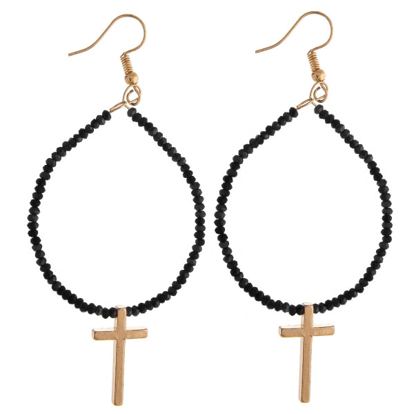 "Metal drop earrings featuring flexible wiring with iridescent beaded details and a cross accent. Approximately 3"" in length."