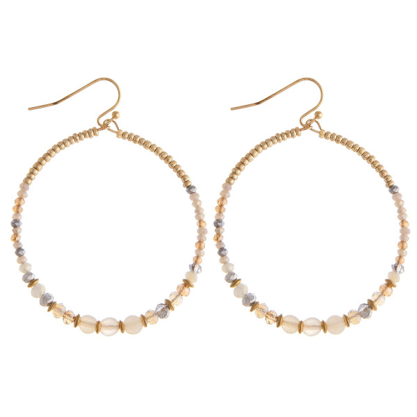 """Circular drop earrings featuring flexible wiring with iridescent beaded details and gold accents. Approximately 2"""" in length."""