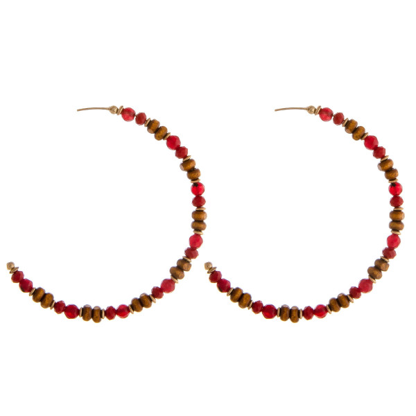 """Large hoop earrings featuring flexible wiring with wood and faceted beaded details and a stud post. Approximately 2.5"""" in diameter."""