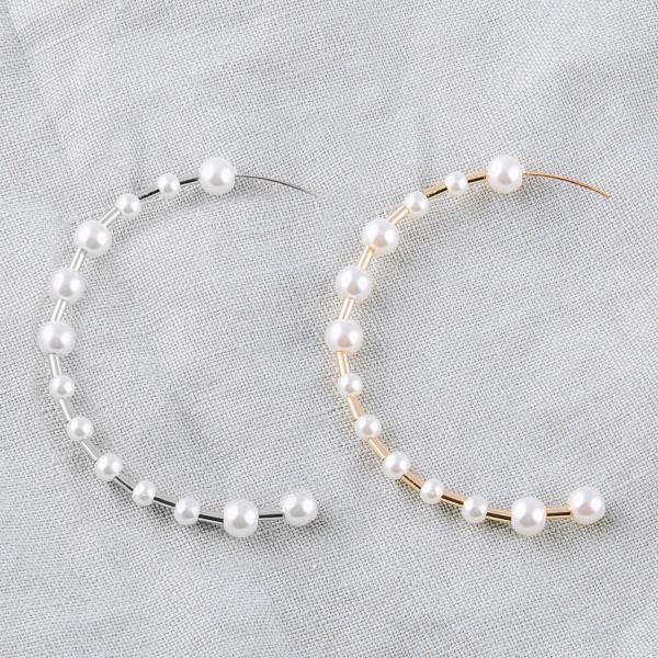 """Large metal hoop earrings featuring pearl bead details. Approximately 2.5"""" in diameter."""