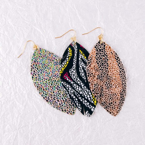 "Faux leather feather earrings featuring animal print details. Approximately 3.5"" in length."
