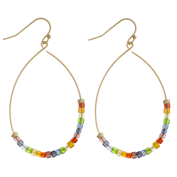 "Dainty gold teardrop earrings featuring multicolor iridescent seed beaded details. Approximately 2"" in length."