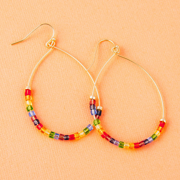 """Dainty gold teardrop earrings featuring multicolor iridescent seed beaded details. Approximately 2"""" in length."""