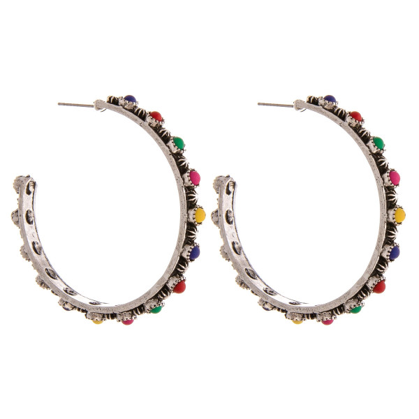"Metal hoop earrings featuring natural stone inspired details and a stud post. Approximately 2"" in diameter."
