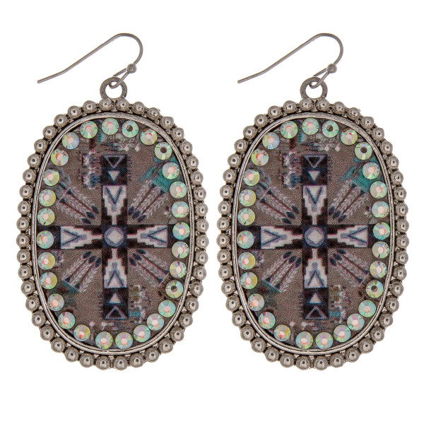 "Metal drop earrings featuring a faux leather cross print center detail with rhinestone accents. Approximately 2.5"" in length."