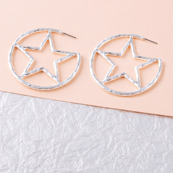 """Silver metal hoop earrings featuring a center star detail with a stud post. Approximately 2"""" in diameter."""