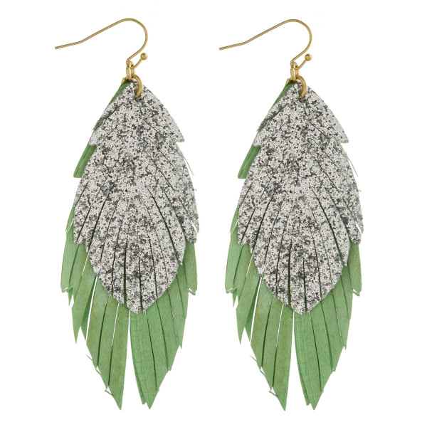 "Double layered genuine leather feather inspired earrings featuring glitter accents. Approximately 3"" in length."