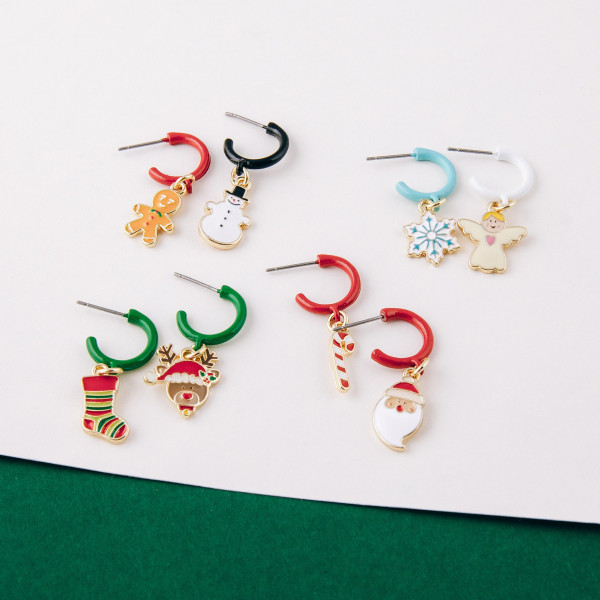 "Enamel coated hoop earring featuring a snowflake accent. Approximately 1"" in length."