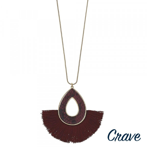 """Long snake chain necklace featuring a metal plated teardrop pendant with faux leather snakeskin details and tassel accents. Pendant approximately 3"""" in length. Approximately 34"""" in  length overall."""