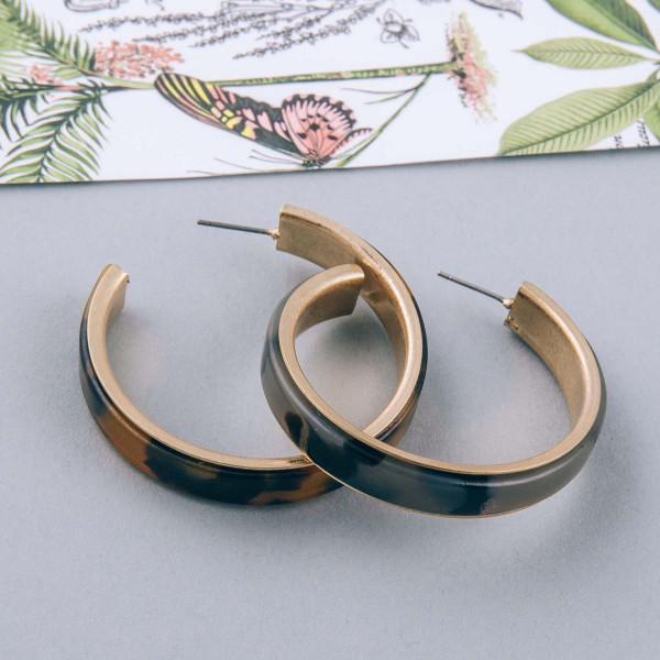 """Metal encased resin open hoop earrings. Approximately 1.75"""" in diameter."""