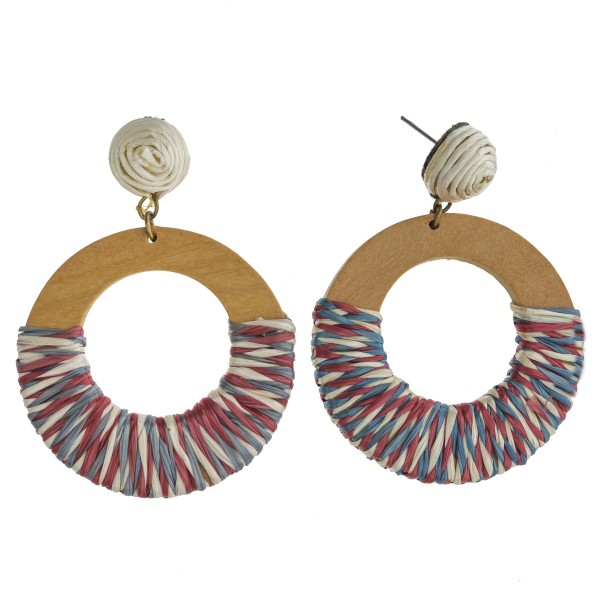 "Raffia wrapped open circle wood earrings. Approximately 2.5"" in length and 1.75"" in diameter."