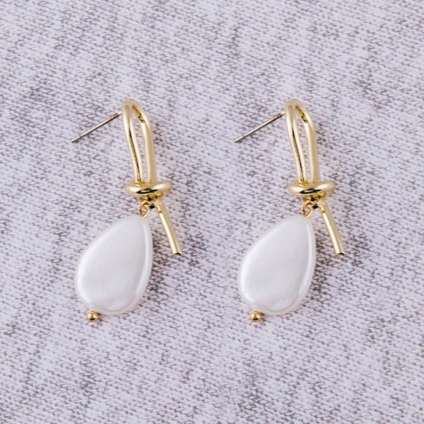 """Gold knotted faux pearl stud dangle earrings. Approximately 1.5"""" in length."""