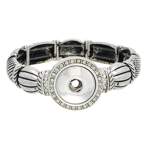 Silver tone stretch bracelet featuring rhinestone decor. Snap on jewelry collection.